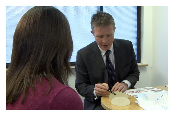 David Oliver talking about breast implants with a patient